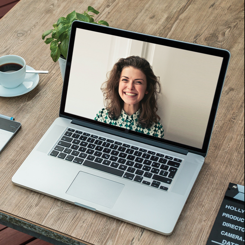 Video conferencing image of a smiling face on the screen of a laptop.